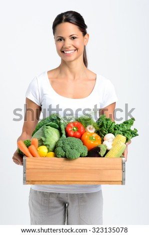 Portrait of happy young woman holding a crate full of fresh organic vegetables on grey background, promoting healthy diet and lifestyle - stock photo