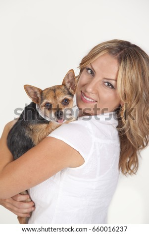Portrait of happy young woman holding chihuahua dog, studio background.