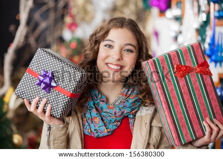 Portrait of happy young woman holding Christmas presents in store