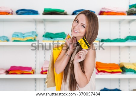 Portrait of happy young woman holding credit card in clothing store - stock photo