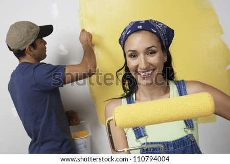 Portrait of happy young woman holding paint roller with man painting wall in background - stock photo