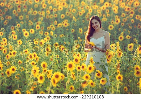 Portrait of happy young woman in a field of sunflowers; copy space - stock photo
