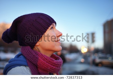 Portrait of happy young woman in city. Shallow DOF. - stock photo