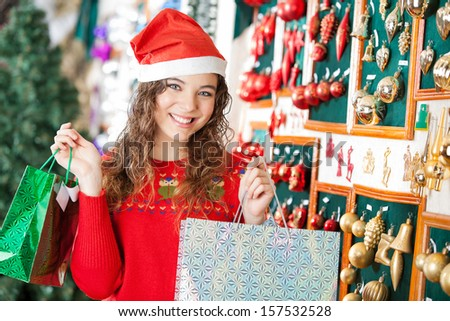 Portrait of happy young woman in Santa hat carrying shopping bags at store - stock photo