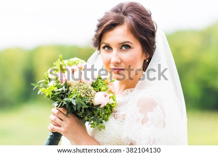 portrait of happy young woman in white wedding dress and bridal veil with flowers - stock photo