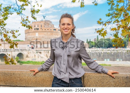 Portrait of happy young woman on embankment near castel sant'angelo in rome italy - stock photo