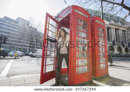 Portrait of happy young woman opening door of telephone booth at London; England; UK - stock photo