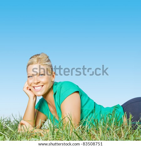 Portrait of happy young woman relaxing on green grass outdoors with copyspace. - stock photo