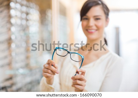 Portrait of happy young woman showing glasses at store - stock photo