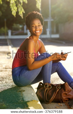 Portrait of happy young woman sitting along a street with a mobile phone on a summer day