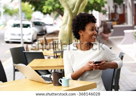 Portrait of happy young woman sitting at cafe with a mobile phone looking away and smiling - stock photo