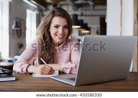 Portrait of happy young woman sitting at cafe with laptop and notebook