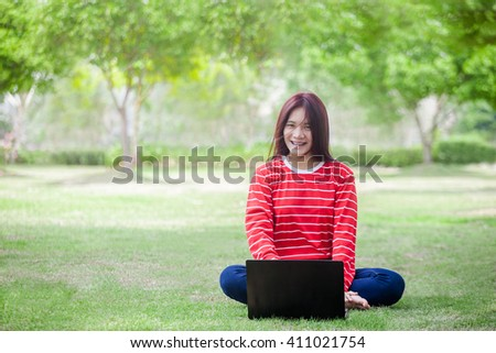 Portrait of happy young woman sitting on grass and using laptop computer - stock photo