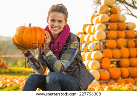 Portrait of happy young woman sitting with pumpkin in front of pumpkin piramide - stock photo