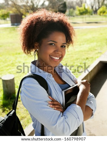 Portrait of happy young woman standing arms crossed on college campus