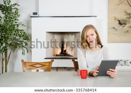 Portrait of happy young woman using digital tablet at table with fireplace in background - stock photo