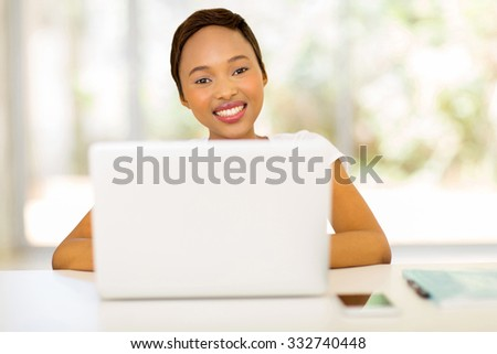 portrait of happy young woman using laptop computer at home - stock photo