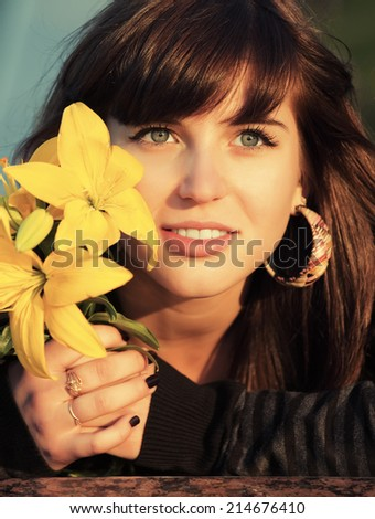 Portrait of happy young woman with a flowers outdoor  - stock photo