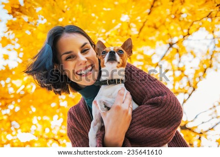 Portrait of happy young woman with dog outdoors in autumn - stock photo