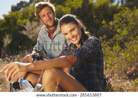 Portrait of happy young woman with her boyfriend taking a break on a hike. Couple hiking on summer vacation, Woman looking at camera smiling with man sitting behind.