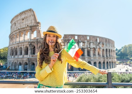 Portrait of happy young woman with italian flag in front of colosseum in rome, italy - stock photo
