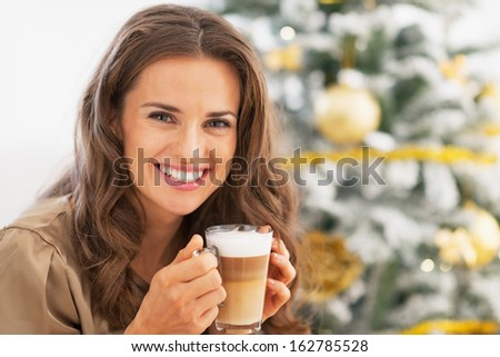 Portrait of happy young woman with latte macchiato in front of christmas tree
