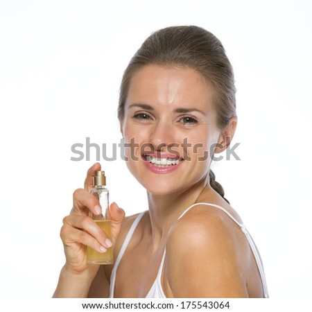 Portrait of happy young woman with perfume bottle - stock photo