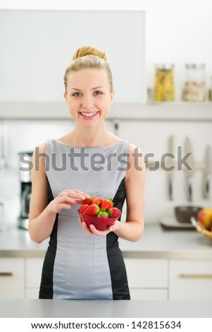 Portrait of happy young woman with plate of strawberries in modern kitchen