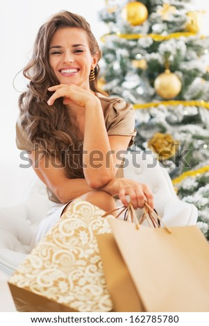 Portrait of happy young woman with shopping bags sitting near christmas tree - stock photo
