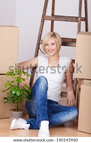 Portrait of happy young woman with stacked cardboard boxes sitting on hardwood floor - stock photo