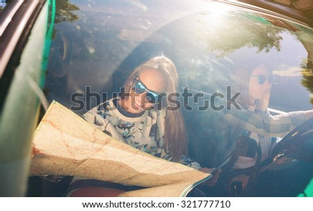 Portrait of happy young woman with sunglasses looking a map inside of car while her friend driving in a road trip adventure. Female friendship and leisure time concept. - stock photo