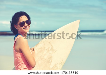Portrait of happy young woman with surfboard at the beach - stock photo