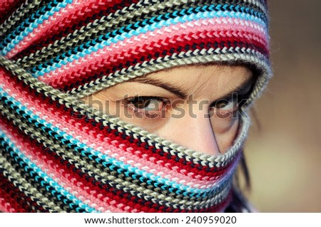Portrait of hard  looking  young woman in motley  head scarf close up