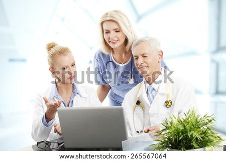 Portrait of health care medical team sitting in front of computer while consulting. Female doctor and male doctor sitting at desk while medical assistant standing at background. - stock photo