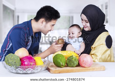 Portrait of healthy family with fresh fruits in the kitchen, man give fruit to his son - stock photo
