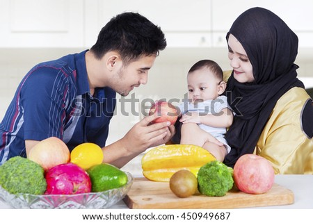 Portrait of healthy family with fresh fruits in the kitchen, man giving apple fruit  to his son
