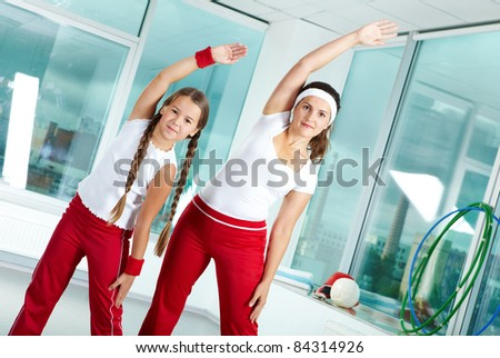 Portrait of healthy female and her daughter practicing physical exercise - stock photo