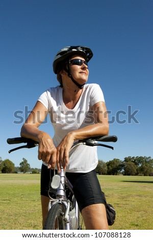 Portrait of healthy fit and sporty, confident and successful mature woman cycling on mountain bike, isolated with blue sky as background and copy space. - stock photo