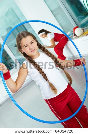 Portrait of healthy girl with blue hoop in gym - stock photo
