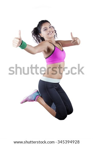 Portrait of healthy indian woman jumping in the studio while wearing sportswear and showing thumbs up - stock photo