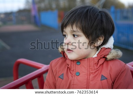 Portrait of healthy little boy playing outside in the playground, Lid boy wearing winter coat playing outdoors