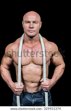 Portrait of healthy man holding rope against black background - stock photo