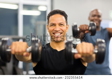 portrait of healthy man working out with dumbbells - stock photo