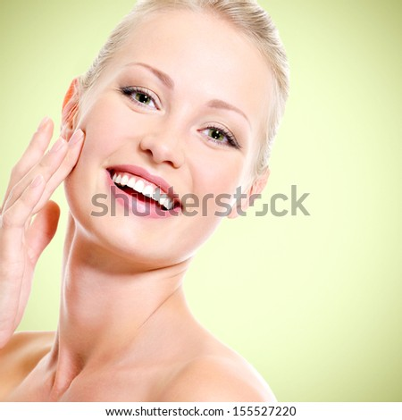 Portrait of healthy smiling woman touching the skin of face - stock photo