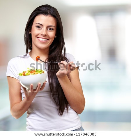 portrait of healthy woman eating salad indoor