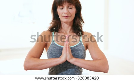 Portrait of healthy woman practicing meditation yoga. Mature caucasian female sitting at the gym with her hands joined meditating in Anjali Mudra yoga pose. - stock photo