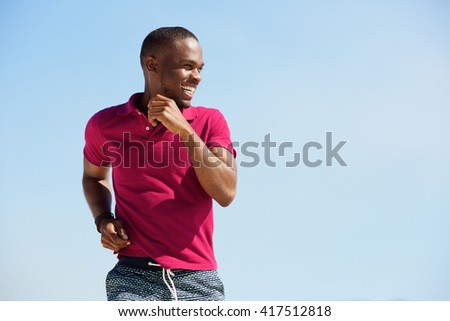 Portrait of healthy young african man running outdoors and smiling - stock photo