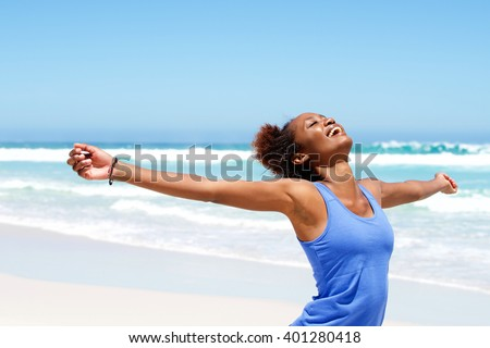 Portrait of healthy young african woman standing on the beach with her hands outstretched - stock photo