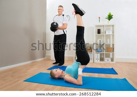 Portrait Of Healthy Young Couple Exercising At Home - stock photo
