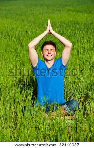 portrait of healthy young man meditation on green grass - stock photo